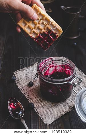 Hand Holding Belgian Waffle With Jam On The Dark Wooden Table. Eating Delicious Dessert