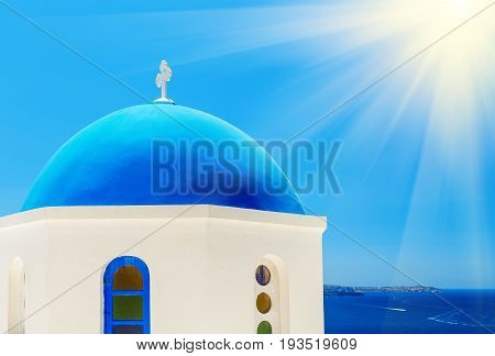 view of orthodox church blue dome and house terrace with flowers at foreground and mountains with sea at background on sunny day with sun shining in right upper corner, Oia, Santorini or Thira, Greece