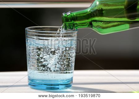 Pouring mineral water in the glass close up image