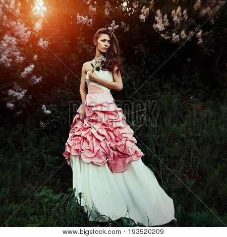Beautiful and elegant woman with branch of lilacs and hair waves wearing wine red and white dress posing outdoors retro vintage style and fashion. She looks like a runaway bride with dramatic emotion