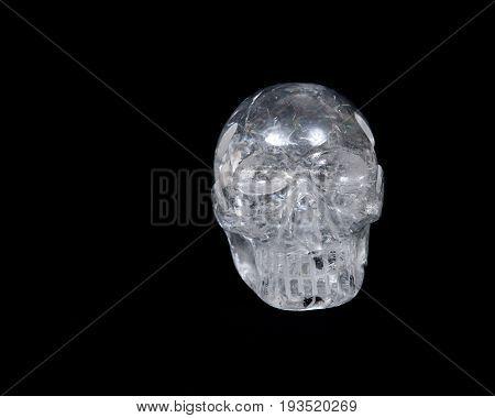 Clear quartz skull with rainbow on black background