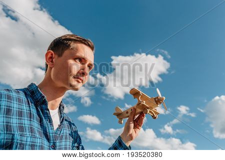 Dreamer, Young man holding in hand wooden toy airplane at blue sky background with copy space. Dreamer and creator concept