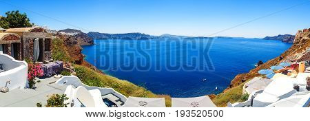 Panorama of Fira, modern capital of the Greek Aegean island, Santorini, with orthodox church, cruise ships, caldera and volcano, Greece
