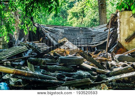 Pile of garbage, trash, ruins and rotten tires, abandoned building after war or earthquake or other natural disaster