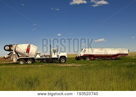An old ready mix cement  and large portable water tanker on wheels is parked on the hillside of an open western prairie,