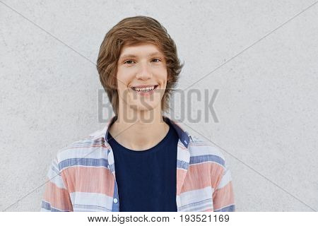 Positive Teenager With Trendy Hairstyle Looking With Dark Eyes In Camera Having Smile And Dimples On