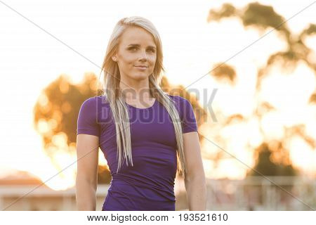 Athletic Female Fitness Model Posing In Her Training Clothes Next To A Tartan Athletics Track