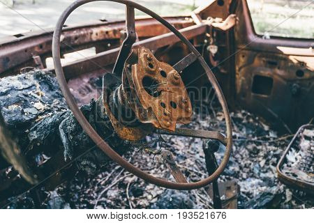 Burned out car, inside view, rusty steering wheel, selective focus on wheel