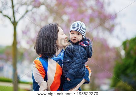 Happy family of two in Paris on a spring day with purple jacarandas in full bloom. Mother and little son enjoying their family time and vacation to France