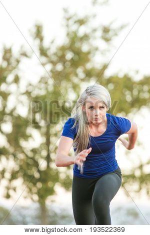Female Athlete Sprinting On A Tartan Athletics Track