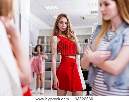 Young slim girl trying on a red crop top and skirt co-ord set looking in the mirror in a clothing shop.