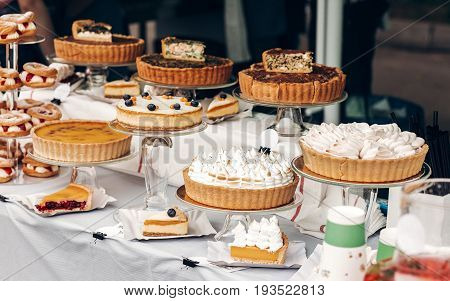 Delicious Cakes And Pie With Whipped Cream On Table At Street Food Festival. Candy Bar With Tasty Sw