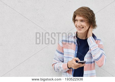 Portrait Of Fashionable Guy With Stylish Hairstyle Wearing Shirt Holding Smartphone Messaging Online