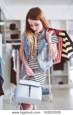 Young female shopper with shopping bags choosing the handbag matching her casual style.