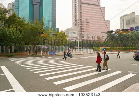 SHENZHEN, CHINA - DECEMBER 12, 2014: people crossing a road in ShenZhen. ShenZhen is regarded as one of the most successful Special Economic Zones.