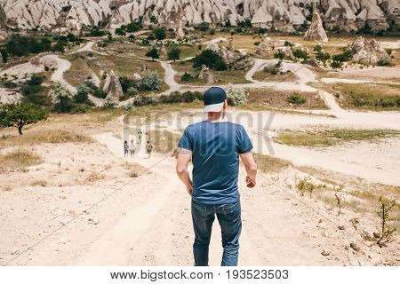 The tourist guy is trying to catch up with his friends of tourists on the road in the hilly countryside of Cappadocia in Turkey. Hiking, travel, walk.