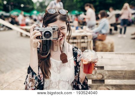 Happy Hipster Woman In Sunglasses Making Photo With Old Camera And Drinking Lemonade. Stylish Boho G