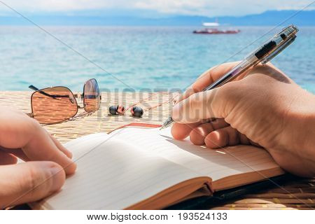 Caucasian Man Is Writing Sime Idea, Message Or Letter In His Notepad By Pen While He Sitting On The