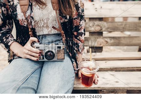 Stylish Hipster Woman Holding Lemonade And Old Photo Camera. Boho Girl In Denim And Bohemian Clothes