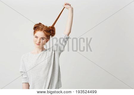 Portrait of young beautiful redhead girl untie bun touching hair over white background. Copy space.