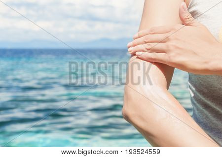 Young Caucasian Woman Applying Sun Protector Cream At Her Hand On The Beach Close To Tropical Turquo
