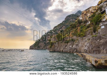 Picturesque view of cliff coast in Positano town at sunset Campania Italy