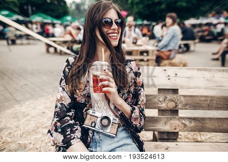 Happy Stylish Hipster Woman In Sunglasses With Lemonade, Smiling. Boho Girl In Denim And Bohemian Cl