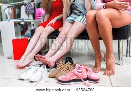 Close-up view of barefoot long slim female legs surrounded by variety of sports shoes. Three female friends sitting resting after shopping in a shopping mall.