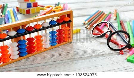 Colorful back to school supplies double border over white table. Mental arithmetic scores abacus Flat lay style