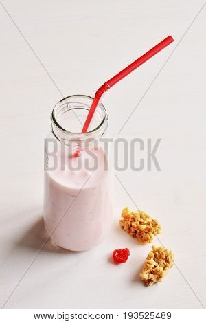 cherry yogurt drink in small glass bottle with red straw, dry berries and wholegrain crunchy against white wooden background