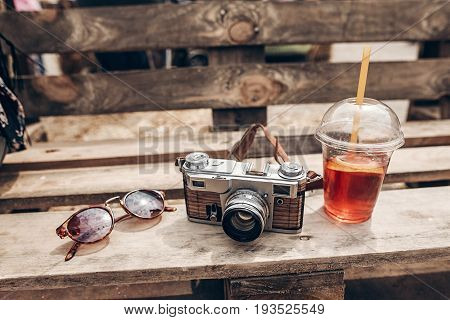 Sunglasses Camera And Lemonade Cup On Wooden Background At Summer Street Food Festival. Space For Te