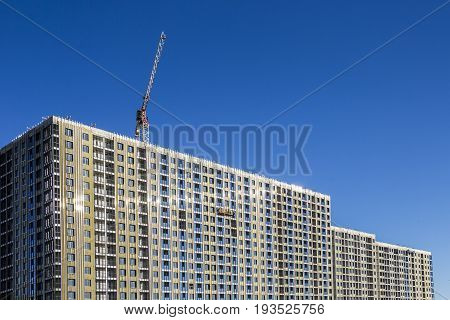 Construction decoration work of the facade by builders in a construction cradle of new residential buildings and tower cranes