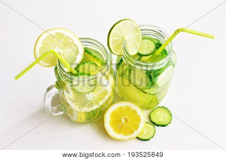 detox water with cucumber, lime and lemon in retro glass jars with straw, time to detox concept