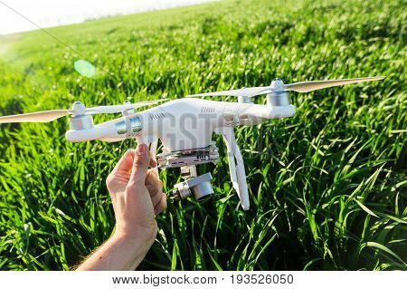 RUSSIA, ROSTOV-ON-DON - APRIL 20, 2017: quadrocopter on takeoff, male hand holding the white drone with build-in camera at background of summer grass field, closeup front view