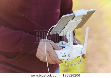 quadcopter flight outdoors, aerial imagery and tech hobby, recreation concept - drone operator hands hold remote control for visual observation of flight and video shooting through tablet PC screen