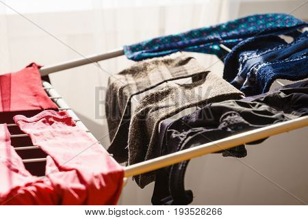 Many colorful clothes from laundry hanging on drying rack at home next to window.