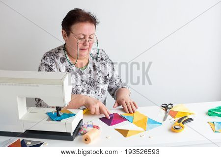 needlework and quilting in the workshop of a tailor woman - elderly women tailor put on the desktop pieces of colored fabric, lay next to the scissors, buttons, pins and thread for sewing machine