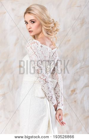 fashionable white gown, beautiful blonde model, bride hairstyle and makeup concept - young charming lady in wedding festive dress standing indoors on light background, pretty woman posing
