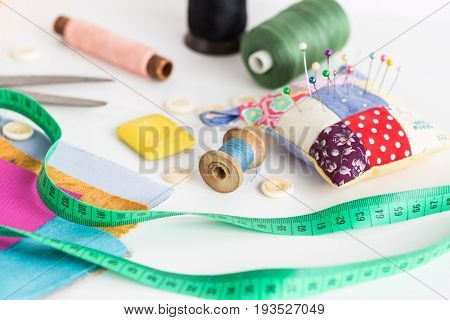 tailoring and fashion concept, patchwork, closeup sewing tools - working environment on a white table, thread spools, buttons, meter, pincushion, scissors, pieces of colored patchwork fabric, soap
