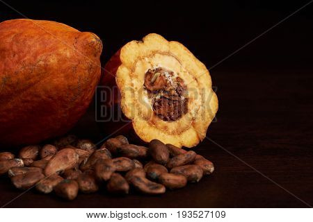Close-up of yellow cacao pod with dry cocoa seeds on wooden background