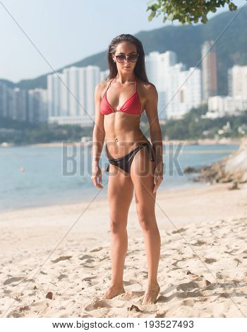 Full-length portrait of confident fitness female model wearing swimsuit standing on sandy beach with high buildings in background.