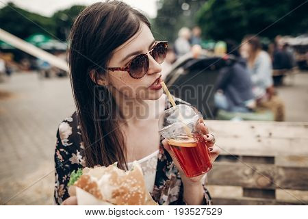 Stylish Hipster Woman Drinking Lemonade. Cool Boho Girl In Denim And Bohemian Clothes, With Cocktail