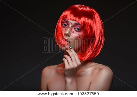 Beautiful young woman in red wig with artistic makeup with golden sparkles. Beauty shot on black background. Colorful nails.