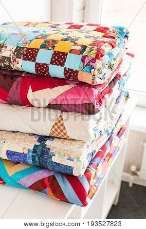 patchwork and fashion concept - beautiful stack of colorful quilts, bedspreads stacked in several rows in height for storage, sale of stitched products on a white background