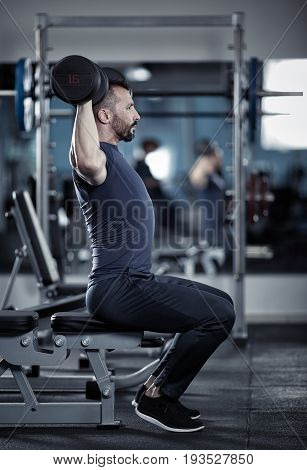 Man doing shoulder workout with dumbbells at gym