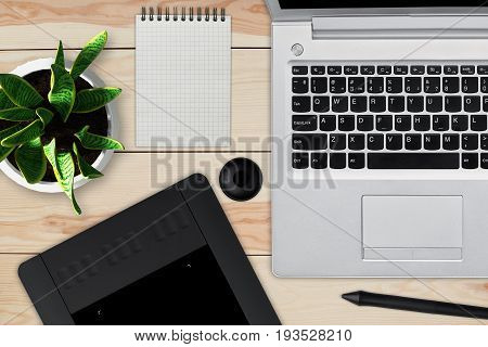 Wooden desk with laptop notepad with blank sheet pot of flower stylus and tablet for retouching. Workspace of professional retoucher. Creativity design art and modern equipments concept