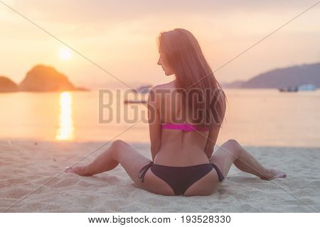 Back view of young female with long brown hair sitting on beach legs spread far apart in black bikini panties admiring sunset and seascape