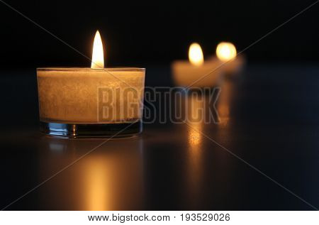 Candlelight and reflexion on black background .