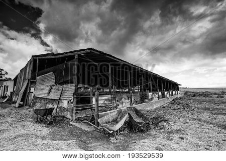 Wide Angle View Of Old Buildings And Farm Instruments On An Old Abandoned Farm