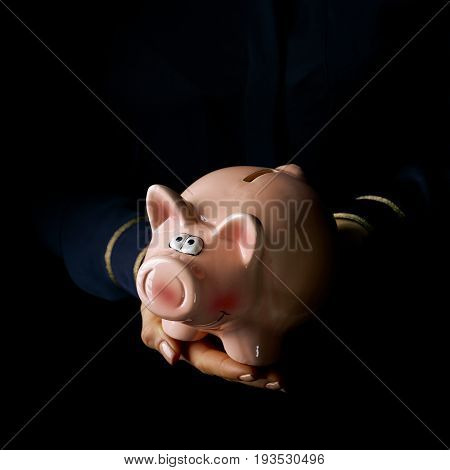 Black Mania. woman hands isolated on black background showing piggy bank